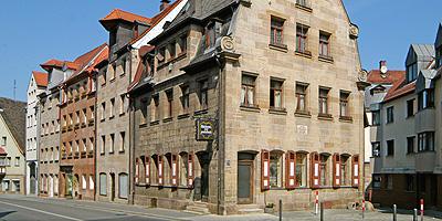 """Das barocke Sandsteinhaus in der Königstraße 27 fällt auf. Es steht mit seinem verzierten Giebel quer zur Straße. Seit 2010 strahlt das Gebäude, in der viele Jahre die Bäckerei """"zur goudn Bäcki"""" untergebracht war,  in neuem Glanz."""